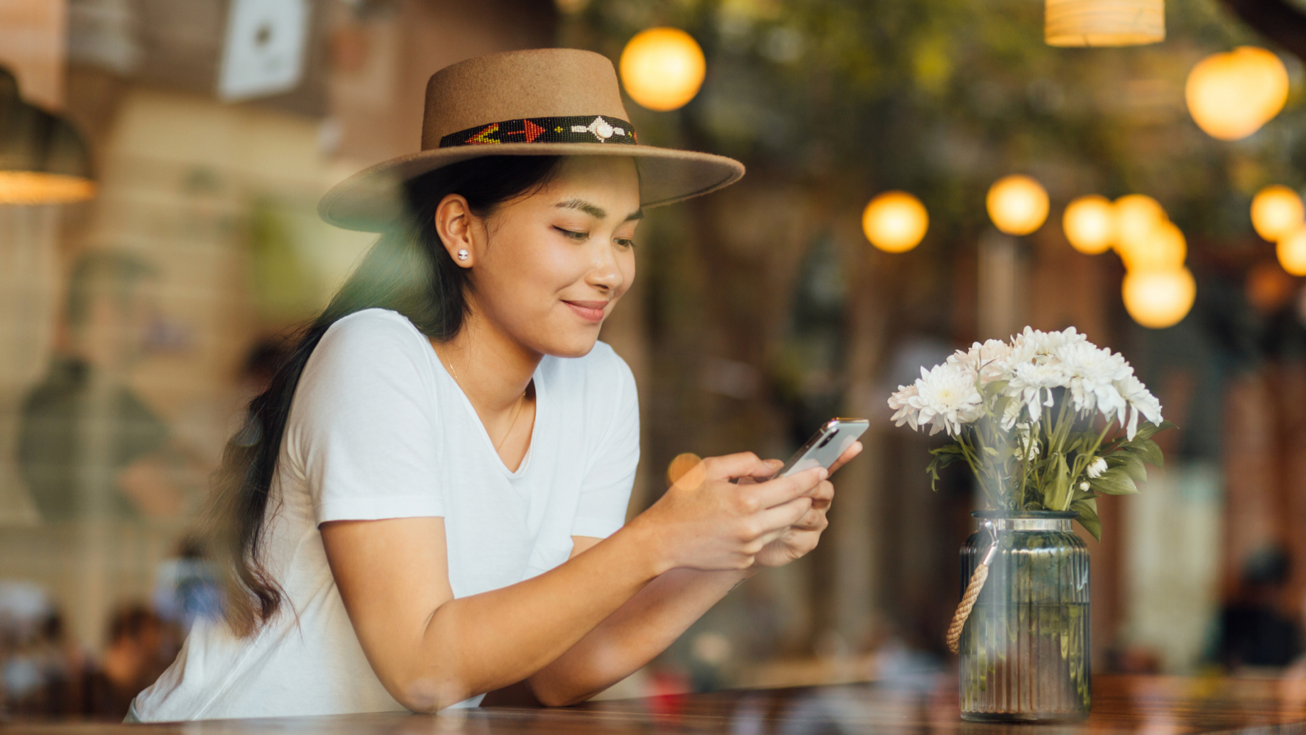 woman with hat sits in a café while watching into her smartphone