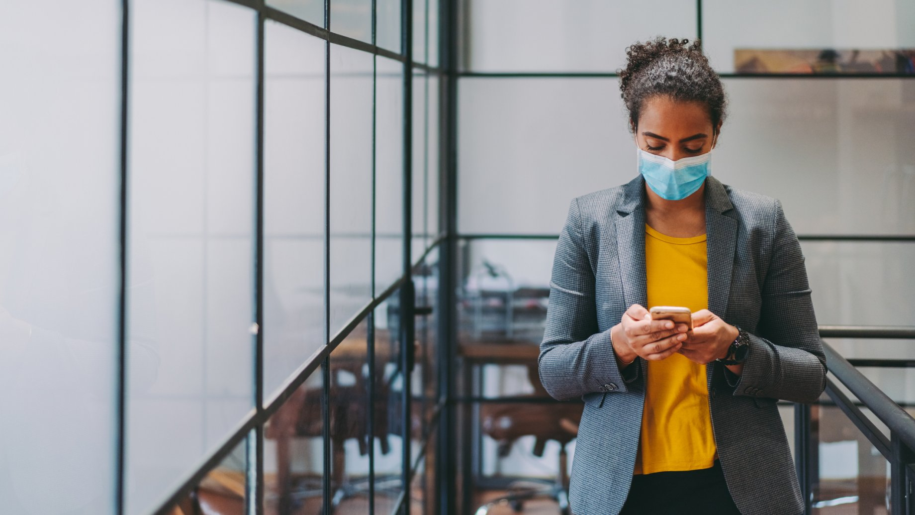 Woman with face mask in a company building looking on her smartphone